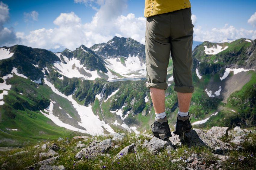 Ein Wanderer mit Wanderschuhen und Blick auf eine Bergkette