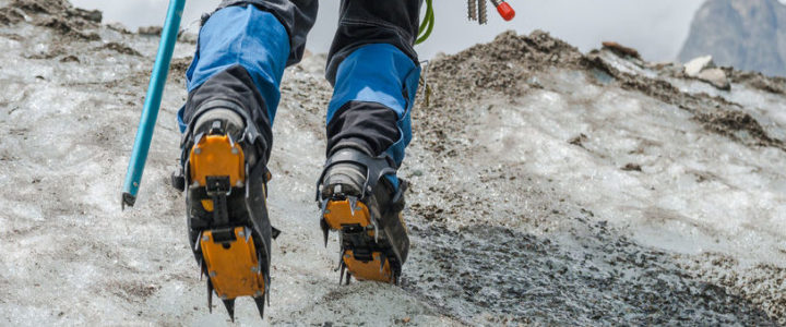 Ein Bergsteiger trägt Gamaschen während er mit Steigeisen über einen Gletscher läuft