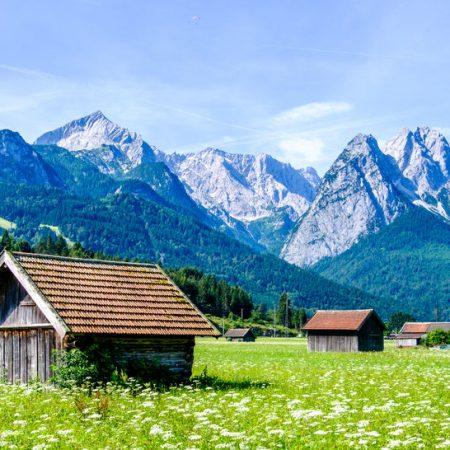 Ein Symbolbild der Höllentalangerhütte mit Waxenstein Alpspitze und Zugspitze im Hintergrund
